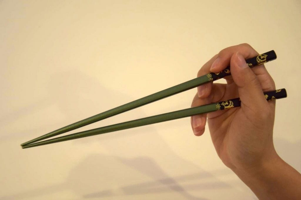 person holding chopsticks - China Tours