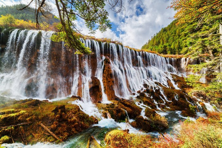 The Nuo Ri Lang Waterfall (Nuorilang) among colorful fall woods in Jiuzhaigou nature reserve (Jiuzhai Valley National Park) of Sichuan province, China. - Tour China